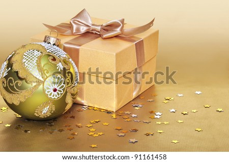 Golden gift box with christmas decoration over gold background