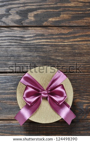Golden gift box with pink ribbon over wooden background