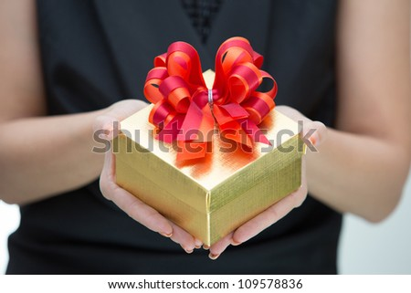 Golden gift box with red and orange satin bow on hand