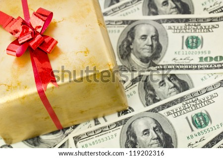 Golden gift box with red ribbon on hundred dollars bills. Holiday concept background