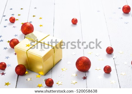golden gift box with star shapes and red christmas balls on white wood table background