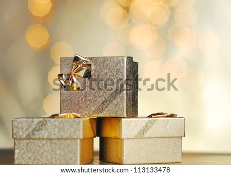 Golden gift on lights background. Golden Christmas.