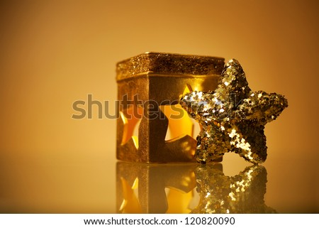 Golden glamour theme with sparkling christmas star and handmade candle holder over light brown background. Studio shot
