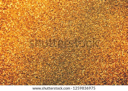 Golden glitter textured background for christmas and new year celebration party. Gold dust sparkling texture top view. Luxury and glamour bronze and brass pattern backdrop.