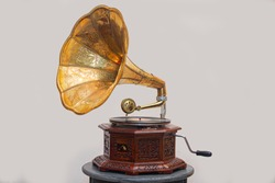 Golden gramophone with disk on wooden box isolated on grey background. Antique brass record player.Gramophone with horn speaker. Retro entertainment concept.Gramophone is an Music device.