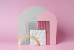 Golden, gray and pink arches with   acrylic and stone plate on a pink background. Stylish background with various materials and geometric shapes