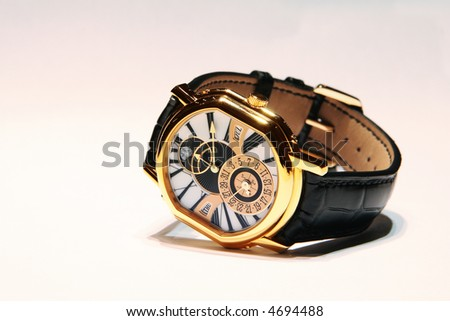 Golden hand made swiss watch on a leather belt, isolated on white background - stock photo