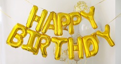 Golden HAPPY BIRTHDAY words made of inflatable balloons on white background