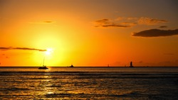 Golden Hawaiian sunset on Waikiki Beach, Honolulu, Oahu.  Photos show beach, sand, shoreline, pacific ocean, boats on horizon, trees over hanging and waves lapping the shore.