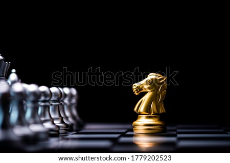 Golden horse chess encounters with silver chess enemy on chess board and black background. Market or business competitor concept. Photo stock ©