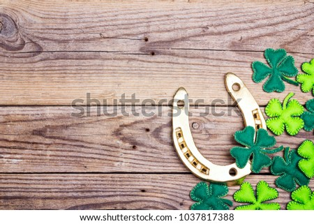 Golden horseshoe and clover leaves on old wooden boards. St.Patrick's day holiday symbol. Space for text.
