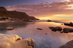 Golden Hour on Camps Bay beach over the tidal pool as purple and orange skies herald the evening light on the Twelve Apostles mountain range