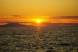 Golden hour on the wavy sea at the fiery orange color tone sunset