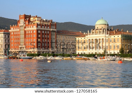 Golden hour over the seafront of Trieste, Italy with 2 imposing and beautiful palaces: Palazzo Aedes (in red) and Palazzo Carciotti.