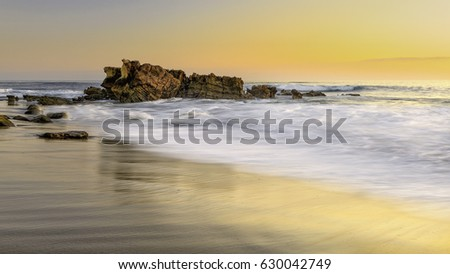Stock Photo Golden Hour sun over a rock formation on a beach in beautiful Southern California.