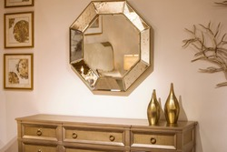 Golden interior, part of the room, a boudoir in gold, a chest of drawers, a mirror, vases, paintings. Modern interior.