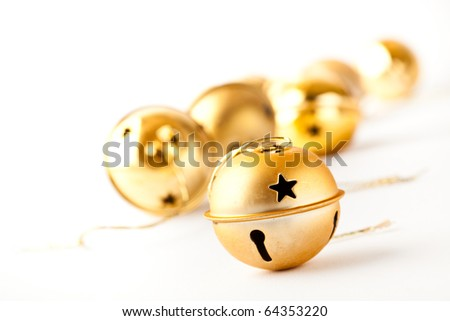 Golden jingle bell Christmas baubles on white