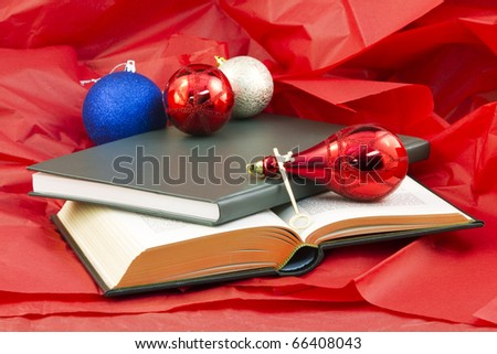 Golden key and open book and closed book on red paper with holiday ornaments reflect the gift that opens knowledge