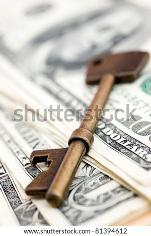 Golden key on top of US dollar bills.