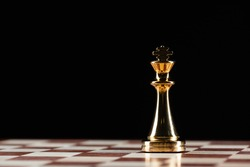Golden king chess figure standing on chessboard. Intellectual and tactic game. Strategy planning, leadership and teamwork business concept. Close-up one gold chess piece on black background.