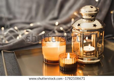 Golden lantern and burning candles on a metal tray. Home decor for muslim holidays such as Ramadan, Eid al Adha, Eid al Fitr Foto d'archivio ©