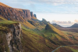 Golden light at sunset or sunrise over colourful landscape view of the rugged, otherworldly terrain of the Quiraing on the Isle of Skye, Scotland.