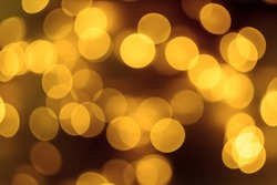 Golden lights of the holiday background. Abstract, bright background, blurred bokeh.