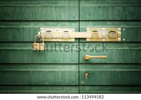Golden lock, padlock and handle on green door, detail
