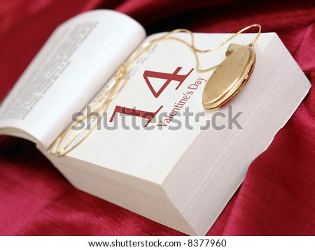 Golden locket put on calendar page indicating Valentine's day over satin background