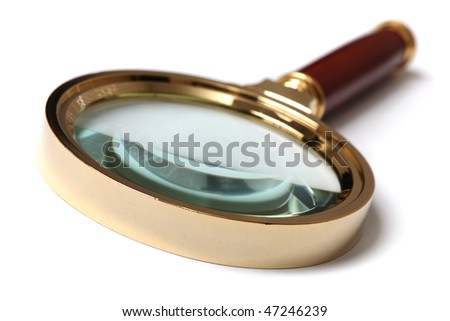 Golden magnifying glass isolated on white background. Tilt, close-up view. Shallow DOF.