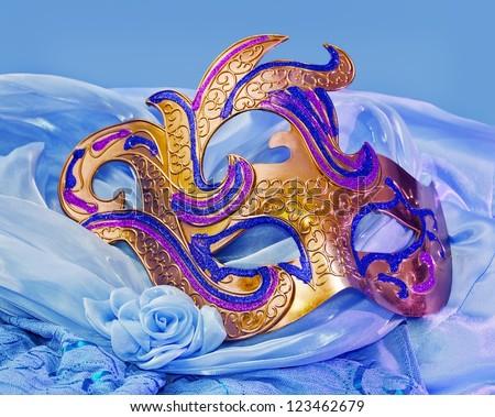 Golden mask on a blue dress