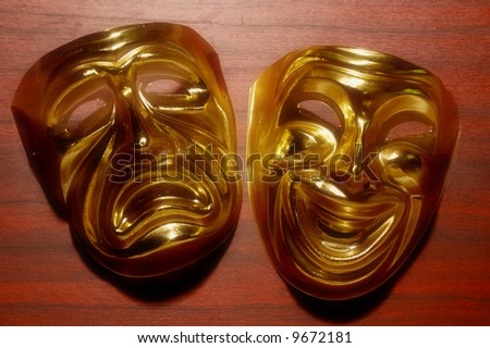 golden masks of comedy and tragedy over a wood surface
