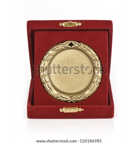 Golden medal in a red velvet box on white background