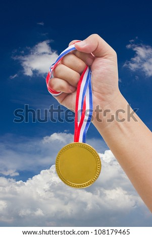 Golden medal in man's hand isolated with blue sky.