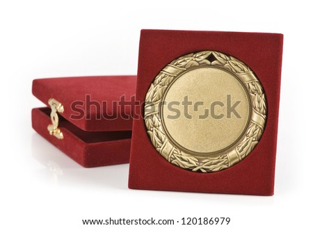 Golden medal with a red velvet box in background