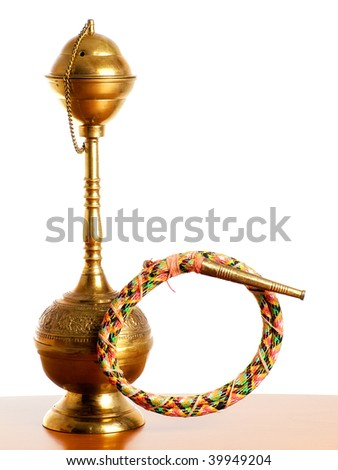 Golden metal narghile or hookah on a bright background.