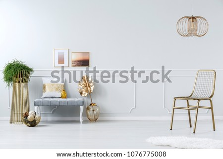 Golden metal net chair, creative design chandelier and an elegant upholstered bench in a bright apartment interior #1076775008