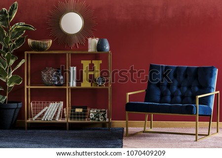 Golden metal rack with books and decor standing in burgundy room interior with navy blue armchair and potted plant