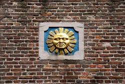 Golden metal sun-face sculpture on the red brick wall