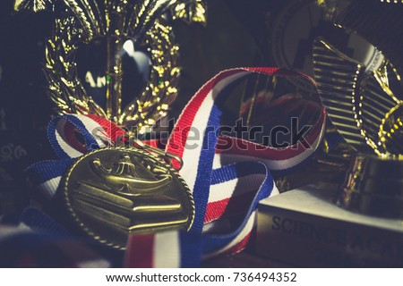 Golden metal with ribbon red white and blue around it laying in between trophies  #736494352