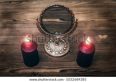 Stock Photo Golden mirror on the magic table between a two burning candles on both side on wooden desk table background. Future reading.