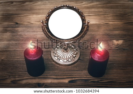 Stock Photo Golden mirror (photo frame) with copy space on the magic table between a two burning candles on both side on wooden desk table background. Future reading.