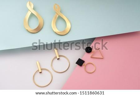 Golden modern stud geometric earrings on colorful background