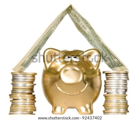 Golden money box pig standing under money home - stock photo