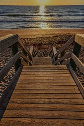 Golden morning sunlight on the grains of sand on a stairway down to a Florida island beach with the beach in the background.