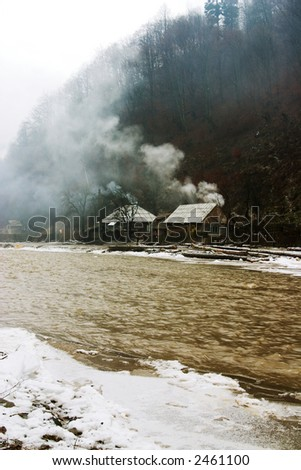 Golden muddy mountain river near houses - stock photo