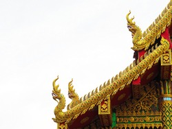 Golden naga statues on temple roof over white background at 