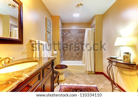 Golden nice bathroom with brown  ceramic tiles and wood cabinet.