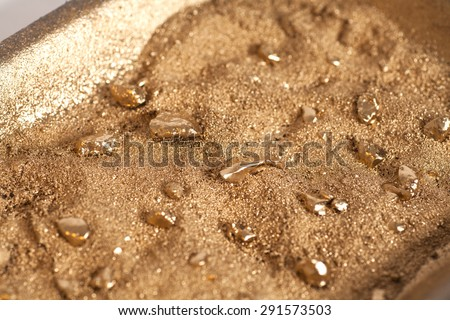 Golden nuggets on grungy wash pan with sand #291573503
