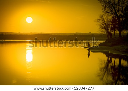 Golden orange sunset over the calm waters of the river.  The silhouette of a fisherman can be seen in the distance.